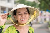 foto of conic  - Senior Vietnamese woman in a conical hat smiling and looking at the camera - JPG