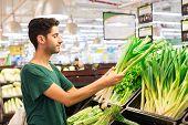 stock photo of leek  - Hispanic man buying leek in the supermarket - JPG