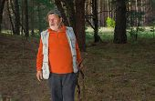 foto of rifle  - Senior ranger with rifle in dark forest - JPG
