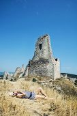 picture of dry grass  - Young woman in a sailor outfit lying on the dry grass and behind is the castle Cachtice - JPG