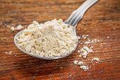 image of quinoa  - tablespoon of gluten free quinoa flour against rustic wood - JPG