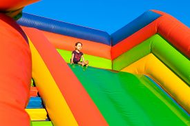 stock photo of inflatable slide  - Little girl sitting on inflatable trampoline - JPG