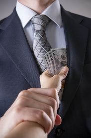 picture of corruption  - Businessman with money in studio on a gray background - JPG