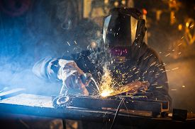 stock photo of sparking  - Welder in action with bright sparks - JPG