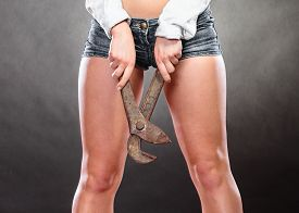picture of gender  - Closeup of sexy woman holding monkey wrench gas grips - JPG