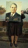 old woman with Brezhnev portrait