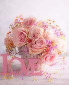 Beautiful pink roses in basket on vintage wooden table. Shabby chic style. Flower composition for ho poster