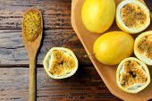 Yellow Passion Fruit And Passion Fruit Cut In Half In Wooden Bowl On Wooden Table. poster