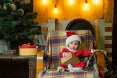Child With A Christmas Present On Wooden Background. Christmas Children. Cute Little Child Is Decora poster