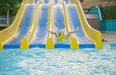 Girl Sliding Water Park. Woman Sliding Down On Water-slide In Aqua Park. poster
