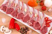 Lamb chops, pepper, mushroom, garlic, shallots, salt, and peppercorn on a wood board