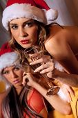 foto of promiscuous  - Portrait of two sexy girls in Santa hats holding the glasses of champagne  - JPG