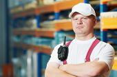 young handsome worker man in uniform in front of warehouse rack arrangement stillages