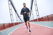 Morning Workout. Full Length Rear View Of Young Man In Sports Clothing Exercising While Jogging On T poster