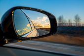 Driving A Car On An Autumn Road With Clouds In The Rear View Mirror poster
