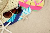 Colorful summer beachwear, flip flops, towel, hat, sunglasses and starfish on sand beach.