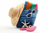 Beach bag with straw hat,towel,flip flops and sunglasses.Isolated on white background.