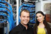 Two administrators, male and female, at server room