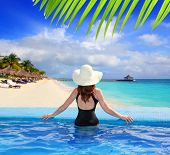 black swimsuit woman rear view in a pool with direct view to tropical Caribbean sea [ photo-illustration]