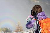 Young Hiking Woman Takes A Picture On The Phone Of Halo Opposite The Sun On Mountain Range Reflectin poster