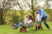 pic of family fun  - Family With Man Giving Mother And Children Ride In Wheelbarrow - JPG