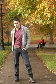 image of teenage boys  - Teenage Boy Standing In Autumn Park With Female Figure On Bench In Background - JPG