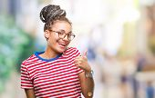 Young braided hair african american girl wearing glasses over isolated background doing happy thumbs poster