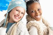 Two Young Women Wearing Warm Winter Clothes Holding Snowball In Studio