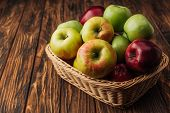 Ripe Multicolored Apples In Wicker Basket On Rustic Wooden Table poster