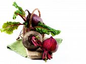 Fresh Organic Beet Roots With Green Beet Tops And One Half In Wicker Basket On Wooden Board And Napk poster