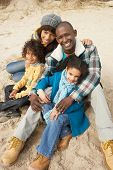 foto of family fun  - Family Sitting On Winter Beach - JPG