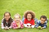image of egg-laying  - Group Of Children Laying On Grass With Easter Eggs - JPG