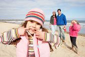 stock photo of family fun  - Family Walking Along Winter Beach - JPG