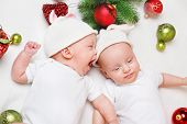Emotional Christmas twin babies in white clothing