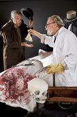 stock photo of jekyll  - Evil doctor reaches over bloody corpse and pays graverobber who tips hat - JPG