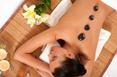 Attractive woman getting spa treatment isolated on white background. Hot Stones Massage