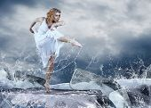 Dance of ballerina on the ice dancepool around splashes of water drops