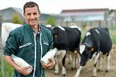 Farmer standing in front of cow herd with bottles of milk