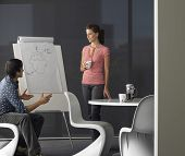 Young businessman giving presentation on flipchart to female colleague in meeting room