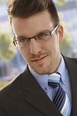 Closeup portrait of elegant businessman smiling, wearing glasses.