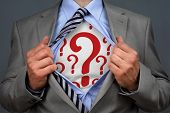Businessman in classic superman pose tearing his shirt open to reveal question mark symbol on chest