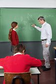 Side view of male teacher teaching geometry to girl with classmate in foreground at classroom
