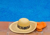 straw hat and sandals by pool side