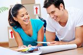 couple lying on floor looking at paint swatch and plans of new house together while drinking coffee and laughing