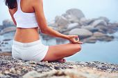 stock photo of stretching exercises  - yoga beach woman doing pose at the ocean for zen health and peaceful lifestyle - JPG
