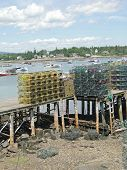 image of lobster boat  - Lobster traps on wharf with boats in harbor on Mount Desert Island Acadia Maine - JPG