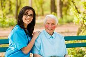 stock photo of sitting a bench  - Kind elderly lady with caring nurse sitting both on bench in a park - JPG