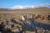 A Rocky Landscape With A Waterfall.