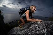 Hiker with backpack climbing natural rocky wall on a dark cloudy background. There are water drops o