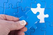Woman's Hand Placing Missing Piece In Jigsaw Puzzle  Signifying Problem Solving